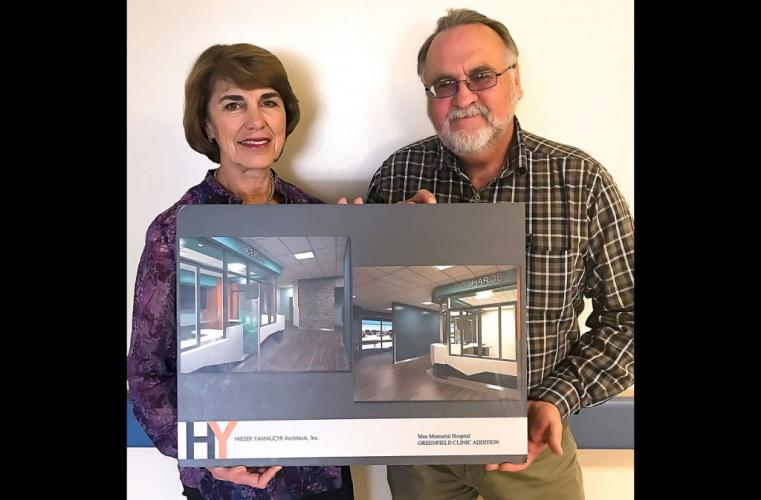 Mee Memorial Hospital CEO Susan Childers and Manager of Plant Operations Jim Johnson hold up renderings of the new Greenfield Clinic expansion.